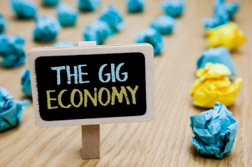 Conceptual hand writing showing The Gig Economy. Business photo text Market of Short-term contracts freelance work temporary poster board with blurry paper lobs laid serially mid yellow lob.